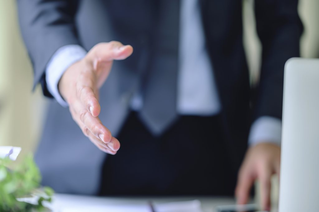 cropped shot of businessmen reaching out hand for shacking.