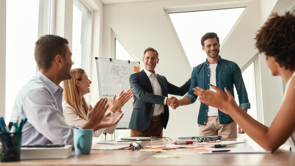 Good job! Two cheerful colleagues shaking hands and smiling while having a meeting in the modern office